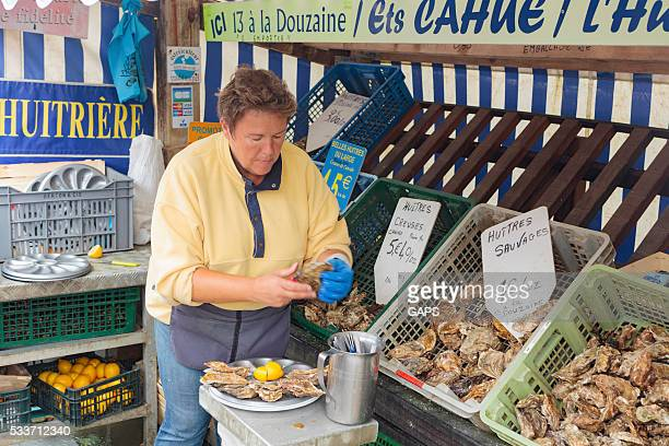 woman preparing the oysters at a local market in France