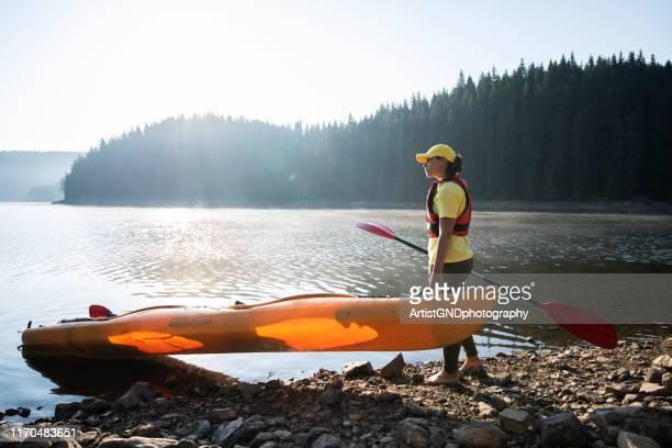 a woman preparing to kayaking in mountain lake. - kayak stock pictures, royalty-free photos & images