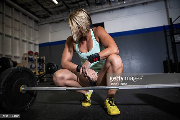 woman preparing to lift weights in gym gym - robb reece stock pictures, royalty-free photos & images