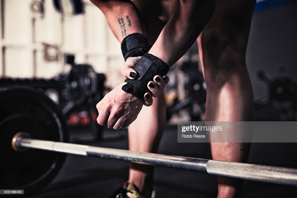 Woman preparing to lift weights in gym gym : Stock Photo
