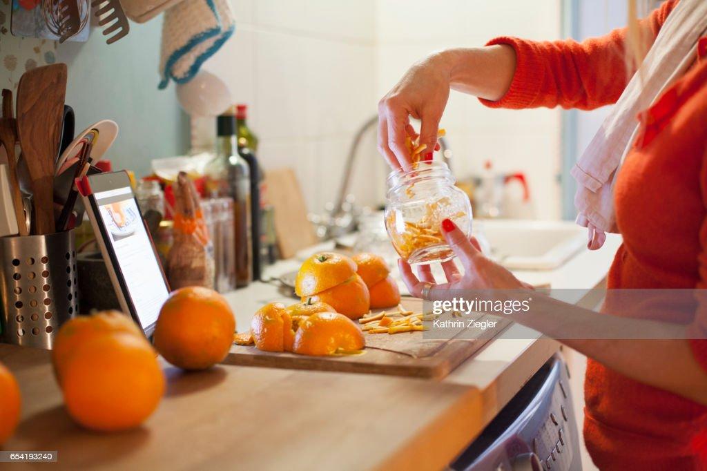 Woman preparing to make orange marmalade, filling jar with thinly cut orange zest : Stock Photo