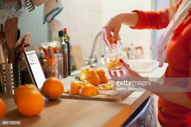 Woman preparing to make orange marmalade, filling jar with thinly cut orange zest
