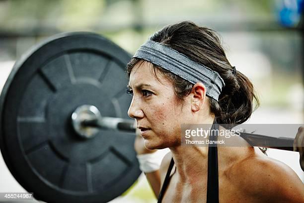 Woman preparing to press barbell overhead