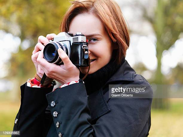 A woman preparing to take a photograph, outdoors, head and shoulders
