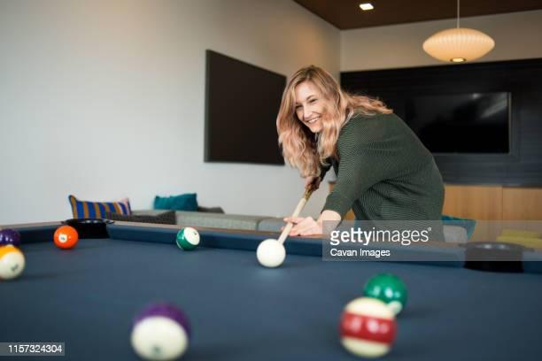 woman preparing to take her shot during game of pool - poolbillard billard stock-fotos und bilder