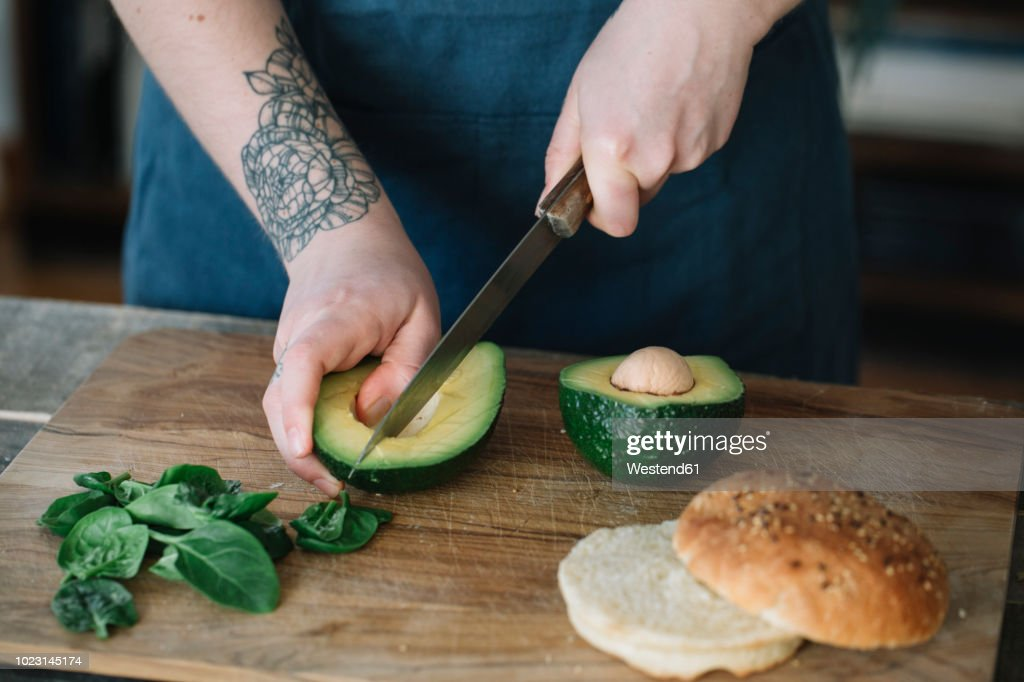 Woman preparing vegan burger, slicing avocado : Stock Photo