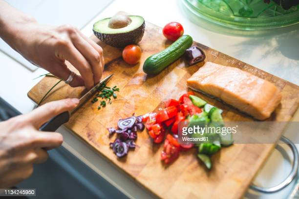 woman preparing vegetables and salmon on chopping board - cutting stock pictures, royalty-free photos & images