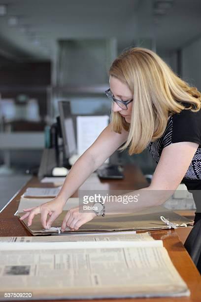 Woman preparing very large newspapers