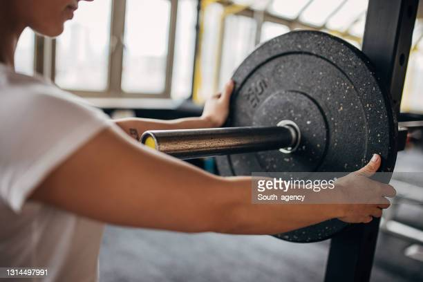 woman preparing weights for training - women's weightlifting stock pictures, royalty-free photos & images