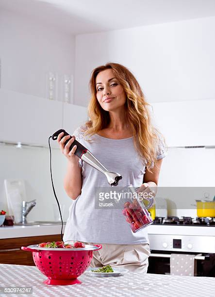 Woman prepering strawberry smoothie juice