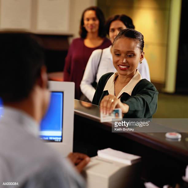 Woman presenting identification at bank (focus on woman)