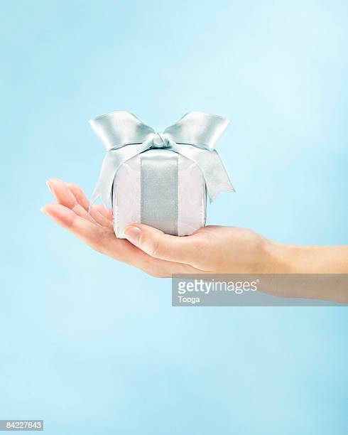 Woman presenting small white and blue gift