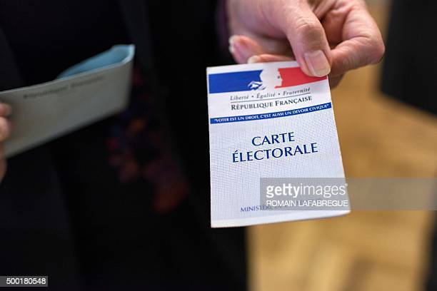 A woman presents her voting card during the first round of the regional elections in the RhoneAlpesAuvergne region on December 6 2015 at a polling...