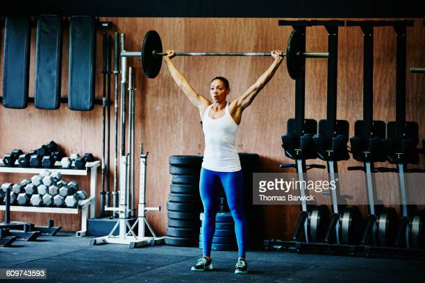woman pressing barbell overhead during workout - barbell stock pictures, royalty-free photos & images