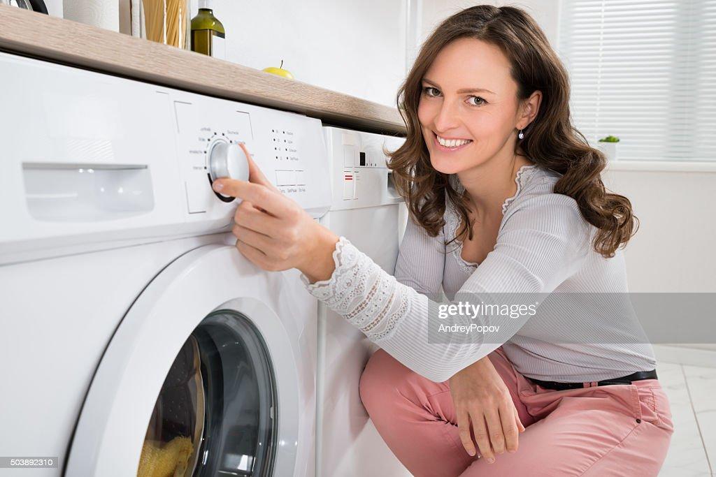 Frau Bügelservice Knopf der Waschmaschine : Stock-Foto