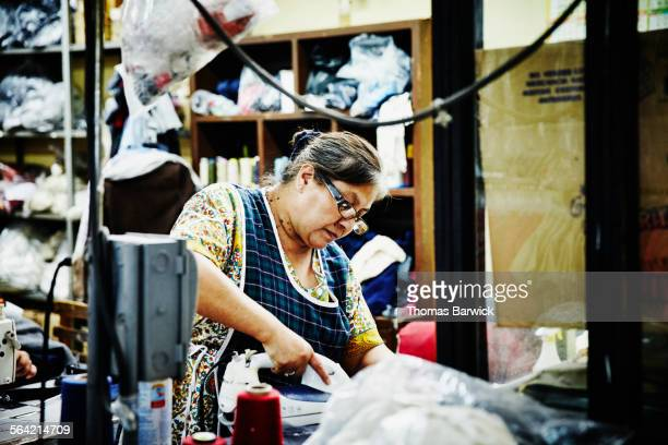 Woman pressing clothing in garment factory