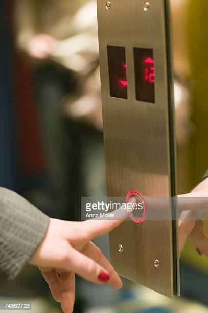 Woman pressing elevator button, close-up