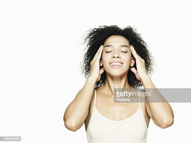 Woman pressing her fingertips on her head