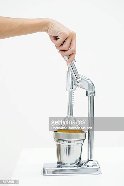 Woman pressing orange with citrus press, cropped view of hand