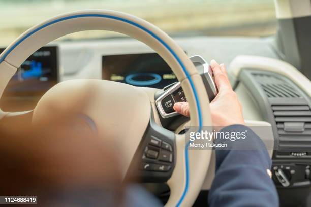 woman pressing start button on electric car - electric car stock photos and pictures