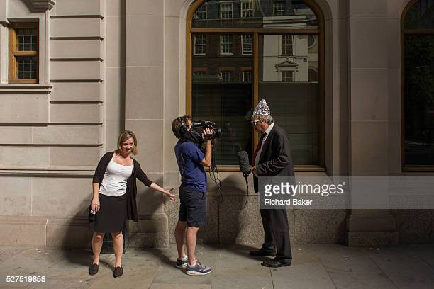 A woman pretends to grope the bottom of a TV cameraman as Londoners experience the unexpected intensity of localised solar rays reflected off the...