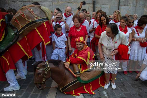 A woman pretends to sit on the back of a 'Zaldiko' during the Comparsa de Gigantes y Cabezudos or Giants and Big Heads parade on the second day of...