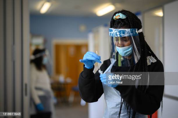 Woman processes a swab test at the Faraday Community Centre asymptomatic COVID-19 test centre on May 18, 2021 in Bedford, England. According to the...