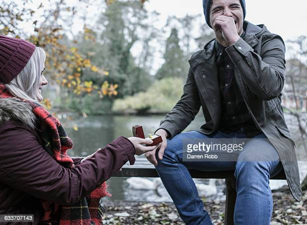 woman proposing to a man on a park bench - fidanzato foto e immagini stock