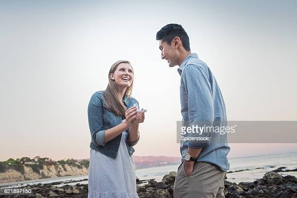 woman propsing to her boyfriend at the beach - engagement stock pictures, royalty-free photos & images