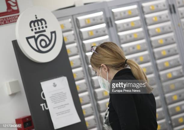 Woman protected with a mask waits for her turn at one of the post offices where Correos company is distributing, through their network of offices,...