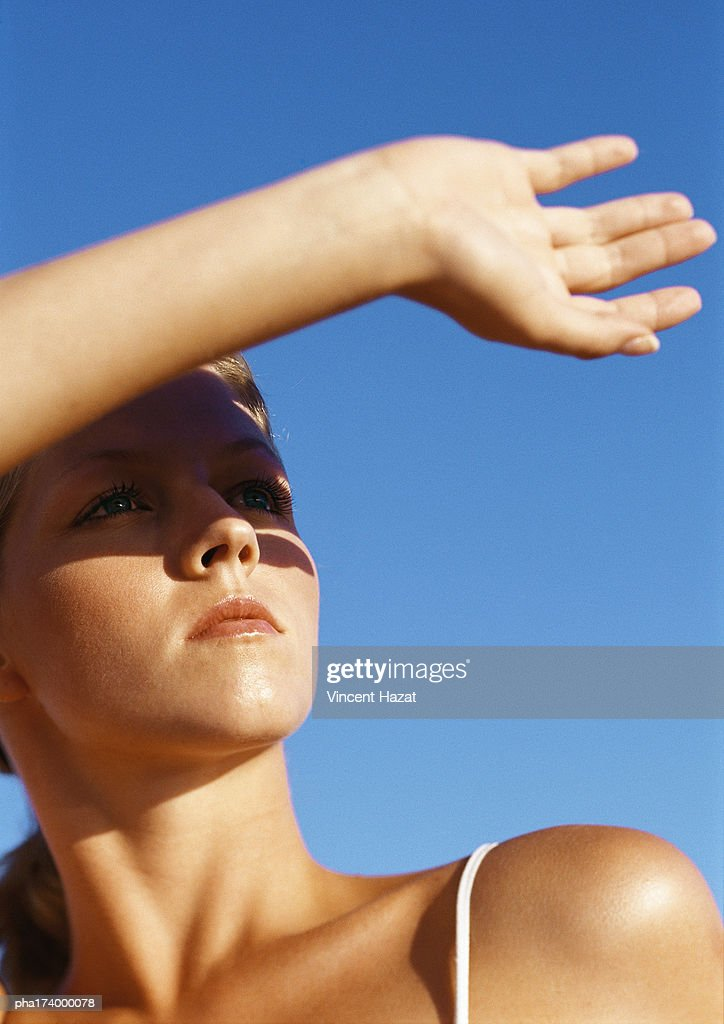 Woman protecting eyes from sun with hand, close-up : Stockfoto
