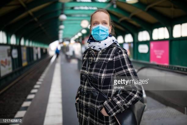 máscara facial protetora da mulher na estação de metrô - plataforma de estação de trem - fotografias e filmes do acervo