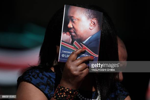 A woman protects her face from the sun using a booklet of Kenya's President Uhuru Kenyatta during the Independence Day ceremony called Jamhuri Day at...