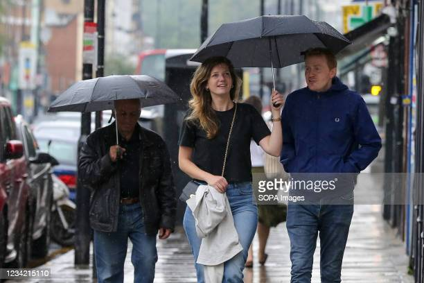 Woman protects herself from rain under an umbrella in London, after the recent heatwave.
