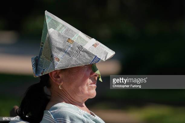 A woman protects herself from the sun with a newspaper hat and nose shade made out of a leaf in the Moscow suburb of Timiryazevskaya during the World...