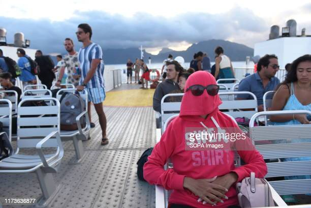 Woman protects herself from the wind with a hood on a ferry near Vaiare port. Moorea is a high island in French Polynesia formed as a volcano around...