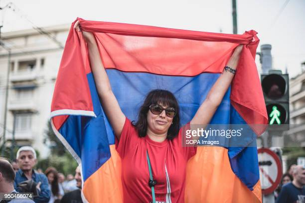 A woman protester holding Armenian flags during a demonstration to mark the 103rd anniversary of the Armenian Genocide by Turkey Protesters marched...