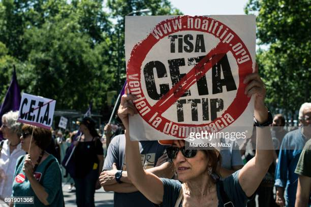 A woman protesting with a placard against CETA trade deal during a demonstration demanding Spanish government not to ratify trade agreement between...