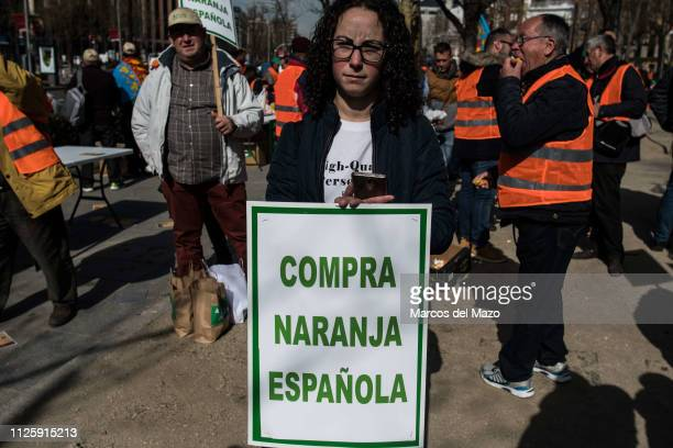 "Woman protesting with a placard that reads ""buy Spanish orange"". Farmers from all over Spain protest at the headquarters of the European Commission..."