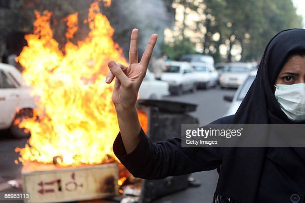 A woman protestor makes a V sign while standing in front of burning rubbish on July 9 2009 in Tehran Iran Following recent unrest in the wake of the...