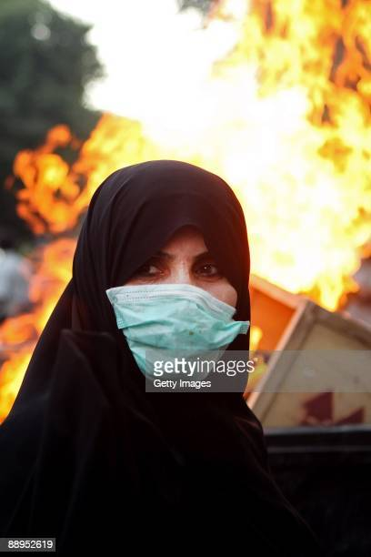 Woman protestor stands in front of burning rubbish while wearing a mask on July 9, 2009 in Tehran, Iran. Following recent unrest in the wake of the...