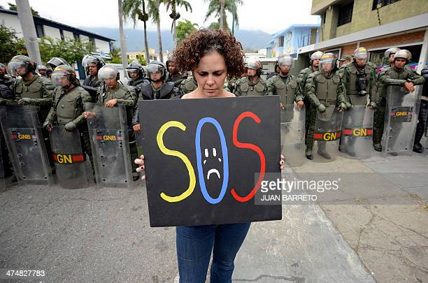 A woman protests against the government of Venezuelan President Nicolas Maduro in front of riot policemen outside the Cuban embassy in Caracas on...