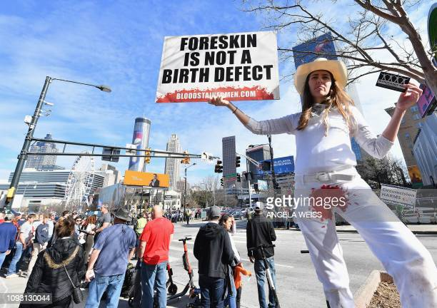 A woman protests circumcision outside the Super Bowl Experience in Atlanta Georgia on February 2 2019 The New England Patriots will meet the Los...