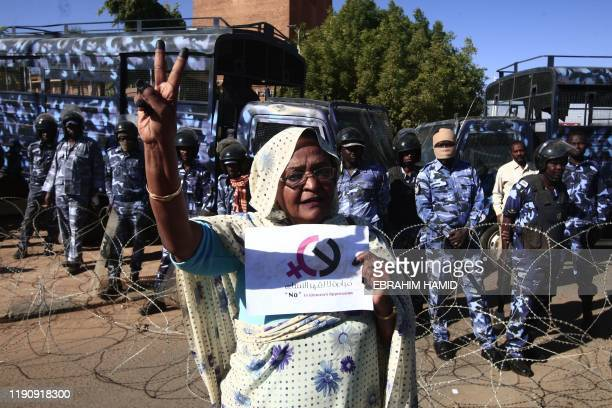 A woman protests in front of the area cordoned off by Sudanese security forces outside a court in Omdurman near the capital Khartoum during the trial...