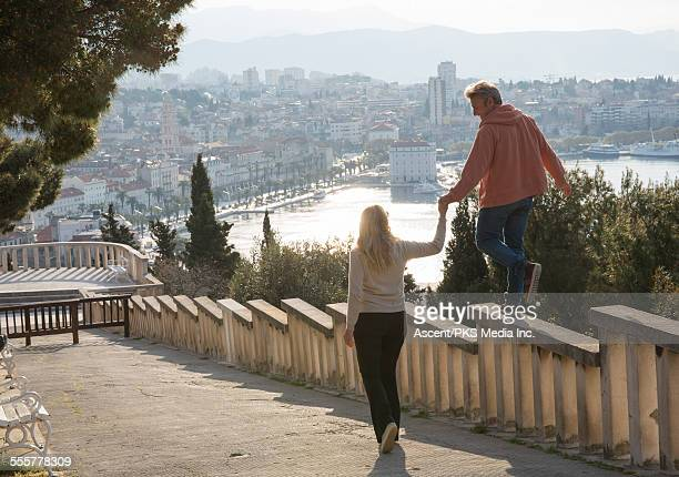 Woman provides hand to man on railing above town