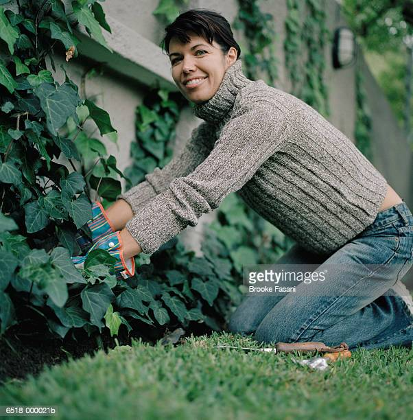 Woman Pruning Ivy on Wall