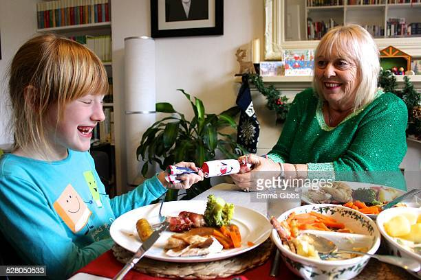 Woman pulling a Christmas cracker with a child