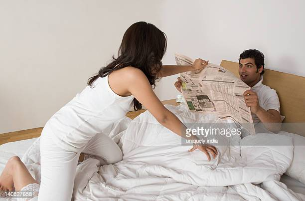 Woman pulling a newspaper from a man on the bed