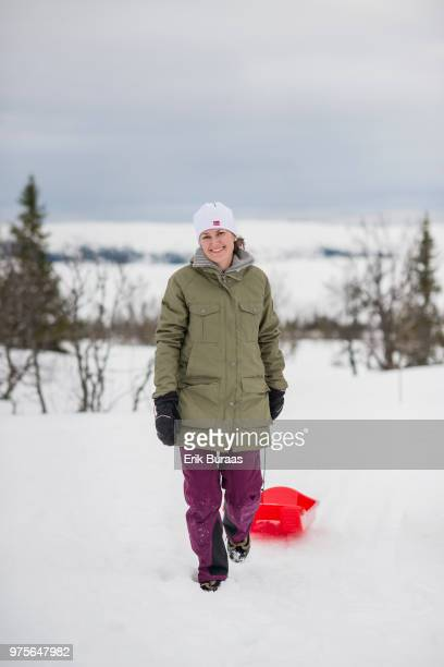 Woman pulling a red plastic sledge