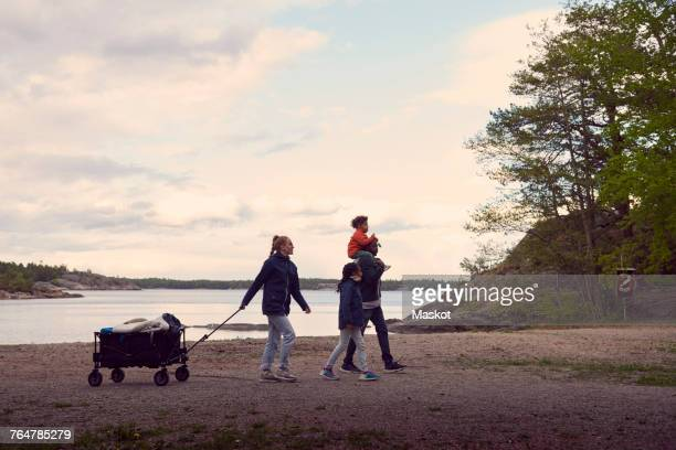 Woman pulling camping cart while walking with family at beach against sky